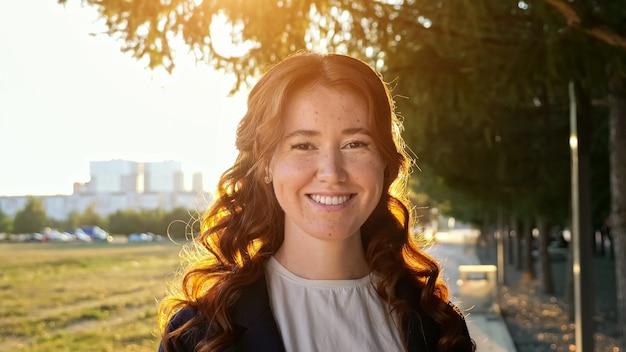 Gelukkige vrouw met krullend haar en sproeten staat bij zonsondergang