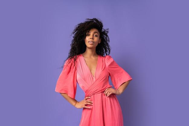 Gelukkige vrouw met krullende haren poseren in stydio over paarse muur. een elegante feestjurk dragen. lente mode-look.