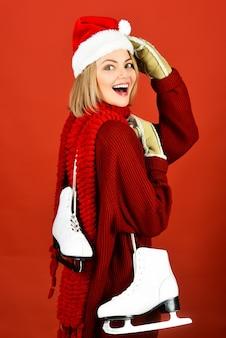 Gelukkige vrouw met kunstschaatsen schaatsen concept lachende vrouw met schaats meisje in santa hat