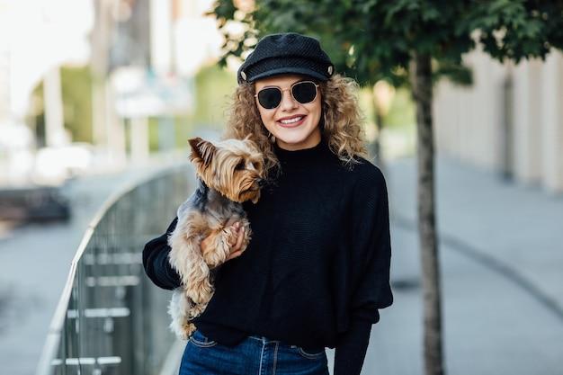 Gelukkige vrouw met lang krullend haar houdt kleine hond vast. mooi meisje knuffelt hondje. dame met puppy. glimlachende aantrekkelijke vrouw met de terriër van yorkshire. meisje met hond in handen. huisdieradoptie, het leven van huisdieren.
