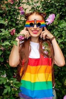 Gelukkige vrouw met lgbt-vlag op haar gezicht die regenboogglazen en het stellen dragen