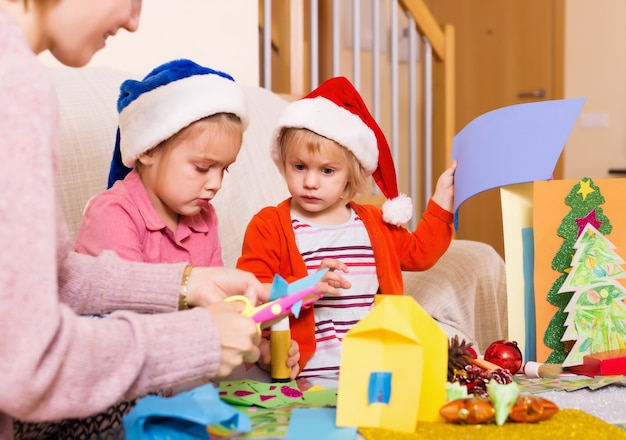 Gelukkige vrouw met meisjes die voor kerstmis voorbereidingen treffen