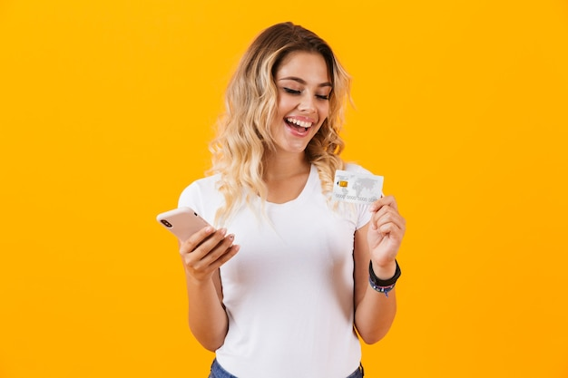 Gelukkige vrouw met mobiele telefoon en creditcard in handen, geïsoleerd over gele muur