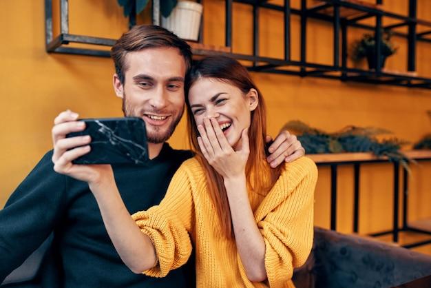 Gelukkige vrouw met mobiele telefoon in de hand aan tafel in de bloempottenstandaard van de koffiekamer