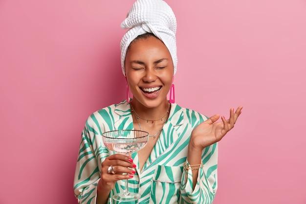 Gelukkige vrouw met natuurlijke schoonheid, donkere huid, verzorgde teint, geniet van huiselijke sfeer, drinkt cocktail na het nemen van bad, gekleed in comfortabele kleding, ontspant thuis