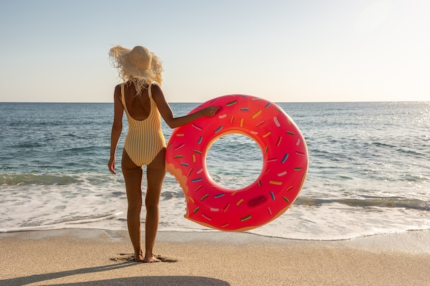Gelukkige vrouw met opblaasbare doughnut op een tropisch strand.