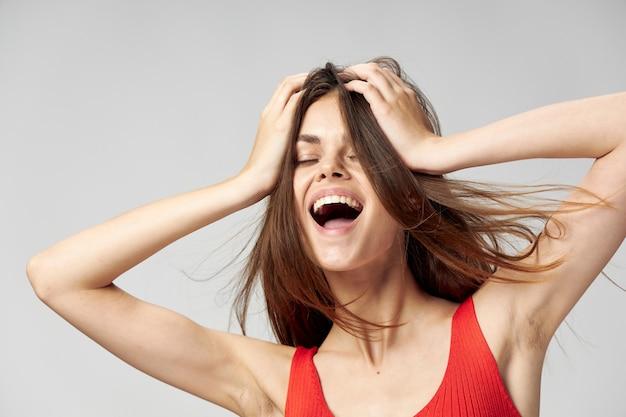 Gelukkige vrouw met open mond houdt handen op gezicht en rood t-shirtlicht