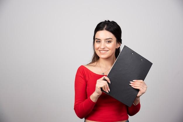 Gelukkige vrouw met pen en klembord op een grijze achtergrond.