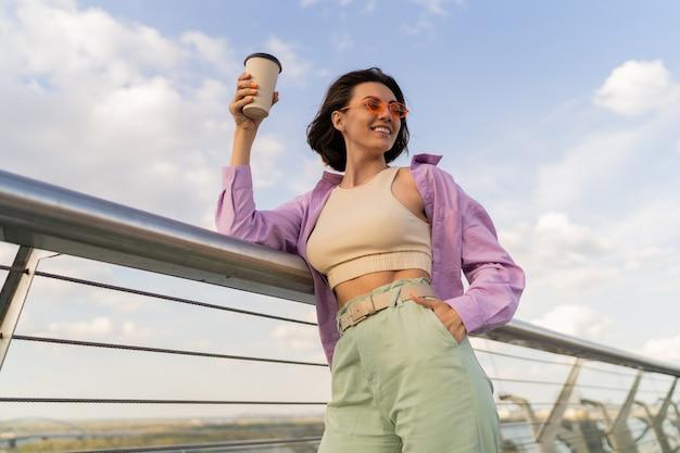 Gelukkige vrouw met perfect figuur in stijlvol paars oversized overhemd genieten van kopje koffie tijdens het wandelen op moderne brug