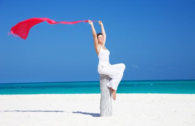 Gelukkige vrouw met rode sarong op het strand