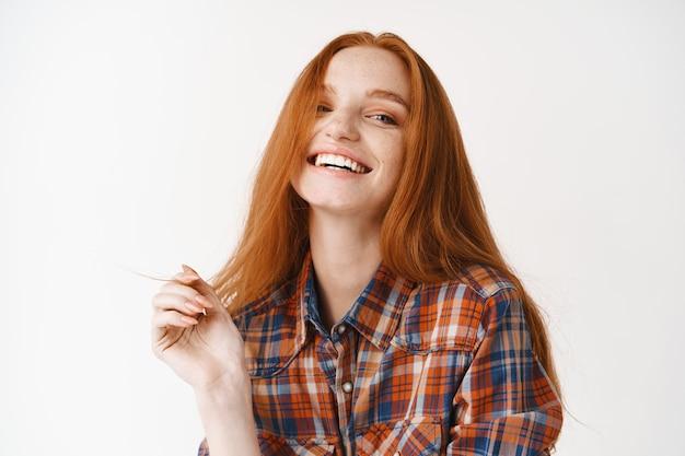Gelukkige vrouw met rood haar, glimlachend en kijkend naar voren, bleke huid met schoon gezicht zonder make-up, witte muur