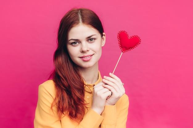 Gelukkige vrouw met rood hart op stok op roze achtergrond en geel overhemd