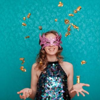 Gelukkige vrouw met roze masker en confettienregen