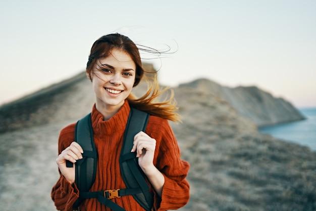 Gelukkige vrouw met rugzak op aard in de bergen dichtbij het overzees en het model van de zonsondergang vreugdevolle glimlach