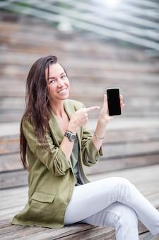 Gelukkige vrouw met smartphone in openlucht in de stad