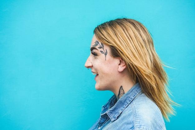 Gelukkige vrouw met tatoeages op haar gezicht