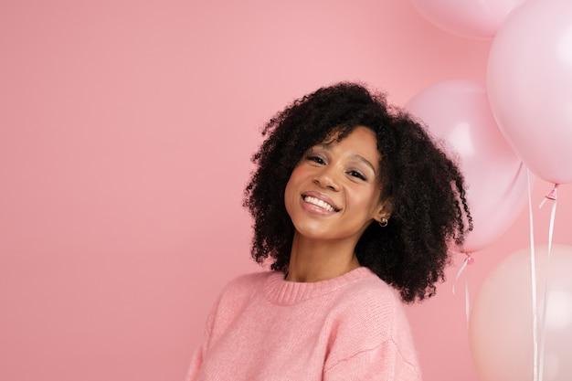 Gelukkige vrouw met veel ballonnen, geniet van cool feest, viert verjaardag, staande over roze muur
