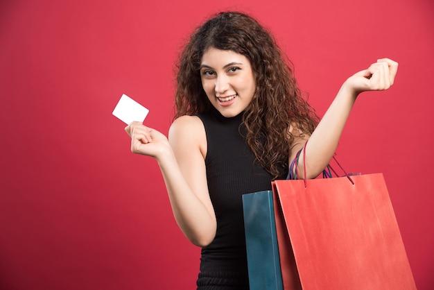 Gelukkige vrouw met veel tassen en bankkaart op rood