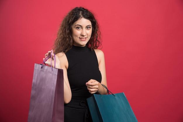 Gelukkige vrouw met veel tassen op rood