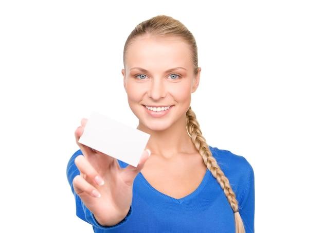Gelukkige vrouw met visitekaartje over witte muur