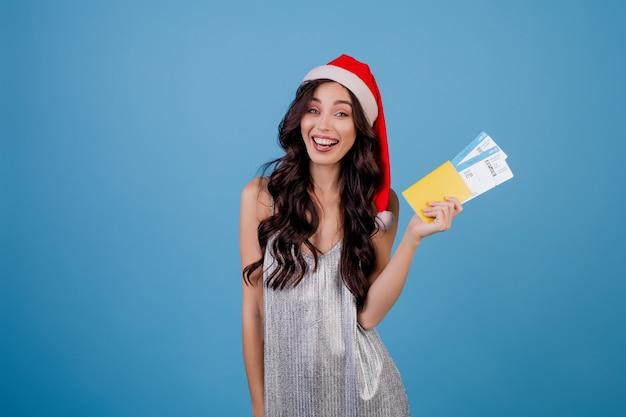 Gelukkige vrouw met vliegtickets en paspoort dat kerstmishoed draagt die over blauw wordt geïsoleerd