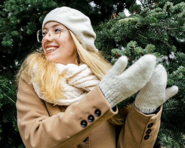 Gelukkige vrouw met wanten die van de sneeuwval genieten in het park in de winter