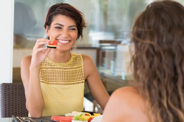 Gelukkige vrouw met watermeloen slice voor vrouwelijke vriend