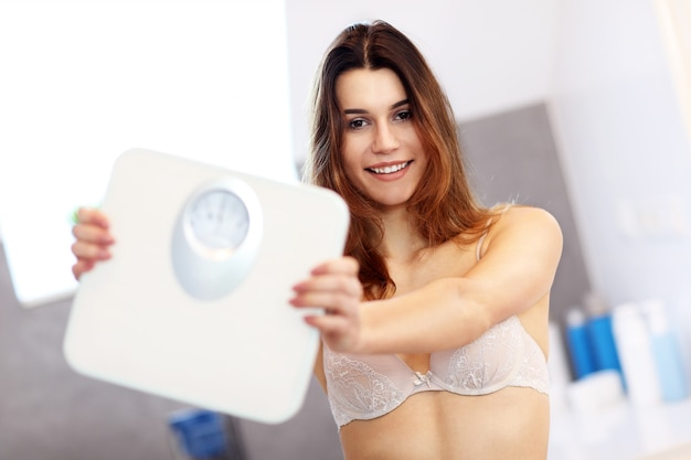 Gelukkige vrouw met weegschaal thuis bathroom