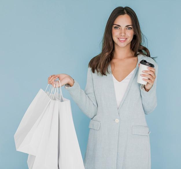 Gelukkige vrouw met witte het winkelen zakken en koffie