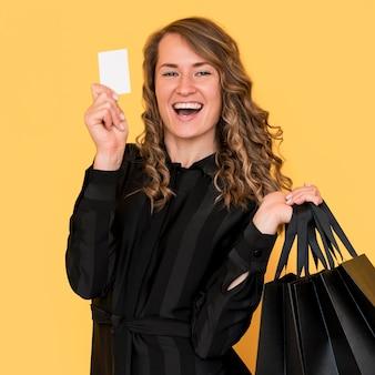 Gelukkige vrouw met zwarte boodschappentassen