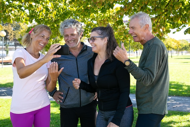 Gelukkige vrouw mobiel scherm tonen aan fitness clubgenoten. blije rijpe vrienden die zich na ochtendoefeningen in park verenigen. pensionering of communicatieconcept
