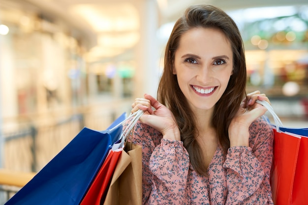 Gelukkige vrouw na grote shopping spree in winkelcentrum