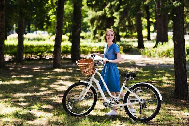 Gelukkige vrouw naast fiets