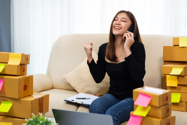 Gelukkige vrouw ondernemer praten op een smartphone en laptopcomputer gebruikt om product online op kantoor aan huis te verkopen