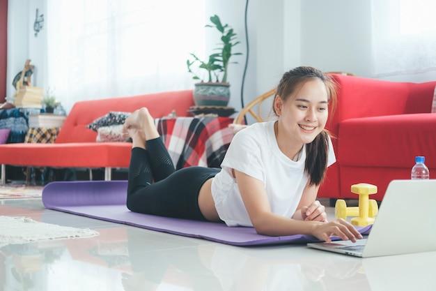 Gelukkige vrouw online tutorial op computer laptop openen voor haar oefening thuis in de woonkamer. blijf thuis en een gezonde levensstijl.