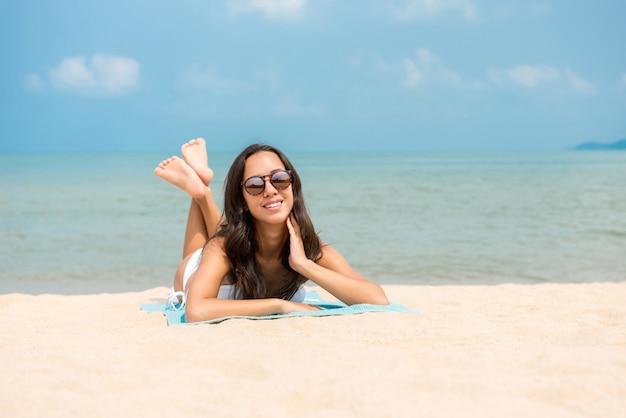 Gelukkige vrouw ontspannen aan het strand in de zomer