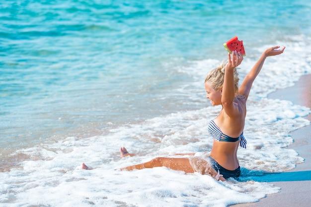 Gelukkige vrouw ontspannen op het strand op een zomerse dag lachend met een plakje watermeloen in haar hand