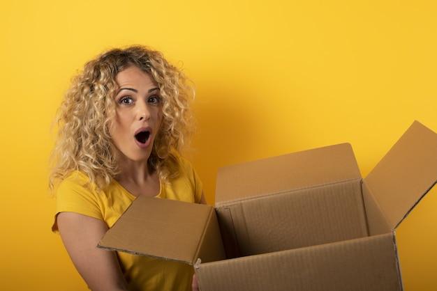 Gelukkige vrouw ontvangt een pakket van online winkelbestelling