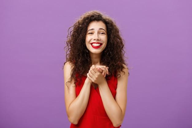 Gelukkige vrouw ontvangt prijs die wordt aangeraakt en opgetogen handpalmen bij elkaar houdt in de buurt van borst glimlachend met...