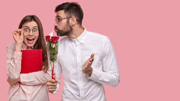 Gelukkige vrouw ontvangt rode rozen van knappe jongen, kijkt positief door bril