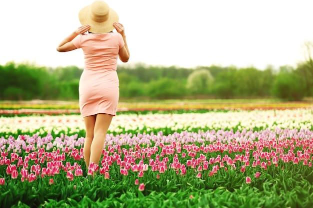 Gelukkige vrouw op bloeiend veld van tulpen