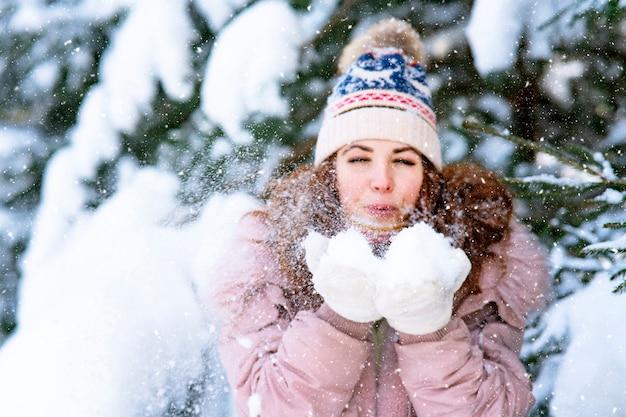 Gelukkige vrouw op de achtergrond van het bos, sneeuw valt op het meisje, de vrouw glimlacht in de winter.