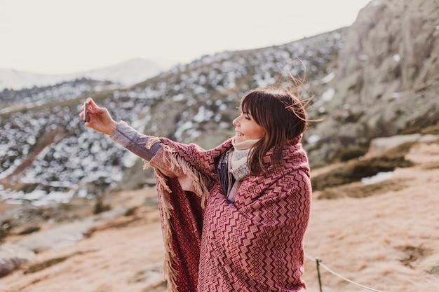 Gelukkige vrouw op de zonsondergang in de natuur in de herfst met behulp van de mobiele telefoon. plezier buitenshuis
