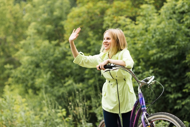 Gelukkige vrouw op fiets zwaaien