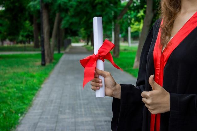 Gelukkige vrouw op haar universiteit van de graduatiedag. onderwijs en duimen omhoog vrouw.