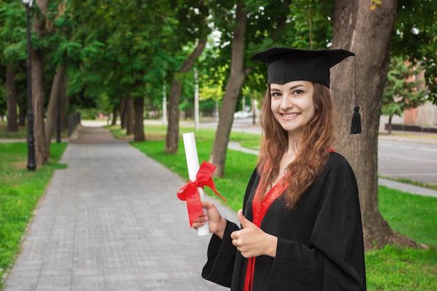 Gelukkige vrouw op haar universiteit van de graduatiedag.