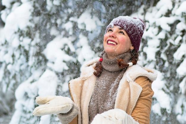 Gelukkige vrouw op het bos, sneeuw valt, de vrouw glimlacht in de winter.