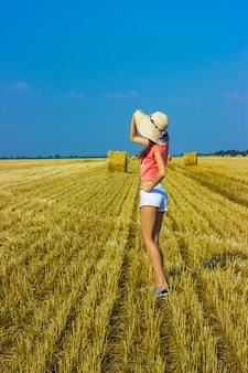 Gelukkige vrouw op hooistapel in zonnige dag. schoonheids romantisch meisje in openlucht tegen hooistapel