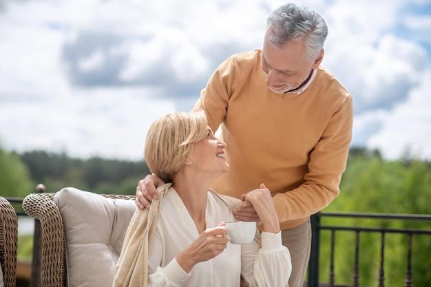 Gelukkige vrouw op middelbare leeftijd die van de zorg van haar echtgenoot geniet