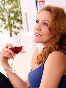 Gelukkige vrouw op middelbare leeftijd geniet van glas wijn